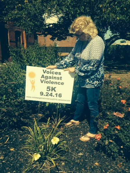 Voices Against Violence Director Mary Gianakis places a lawn sign along the route of the 5 th annual 5K Run/2K Walk to Break the Silence in support of the domestic violence and rape crisis center. The event will be held Saturday, Sept. 24th.